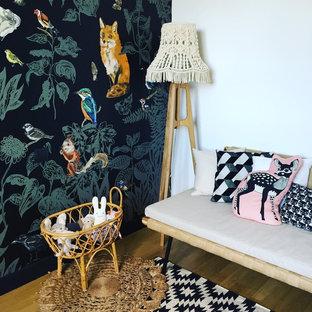 Inspiration pour une petit chambre de bébé neutre nordique avec un mur noir et un sol en bois clair.