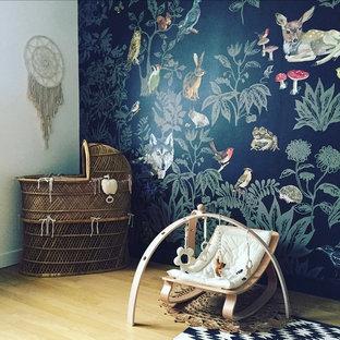 Idées déco pour une petit chambre de bébé neutre scandinave avec un mur noir et un sol en bois clair.