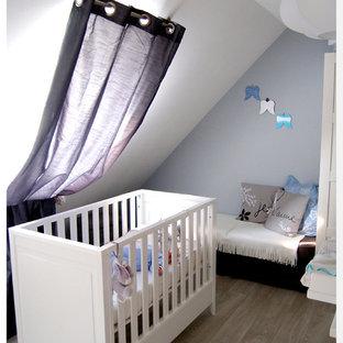Idée de décoration pour une petit chambre de bébé garçon minimaliste avec un mur gris, sol en stratifié et un sol gris.