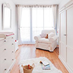 Exemple d'une grand chambre de bébé neutre nature avec un sol en bois clair et un mur blanc.