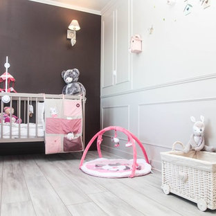 Example of a mid-sized cottage chic girl laminate floor and beige floor nursery design with beige walls