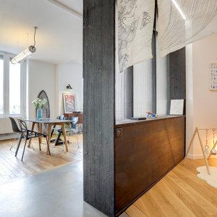 Exemple d'une chambre de bébé neutre tendance de taille moyenne avec un mur noir, un sol en bois clair et un sol beige.