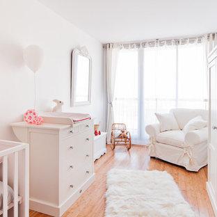 Réalisation d'une grand chambre de bébé neutre tradition avec un mur blanc et un sol en bois brun.
