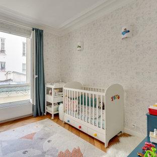 Foto di una piccola cameretta per neonati contemporanea con pareti multicolore, pavimento in legno massello medio, pavimento marrone e carta da parati