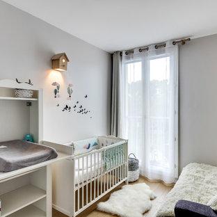 Inspiration pour une chambre de bébé nordique avec un mur gris et un sol en bois brun.