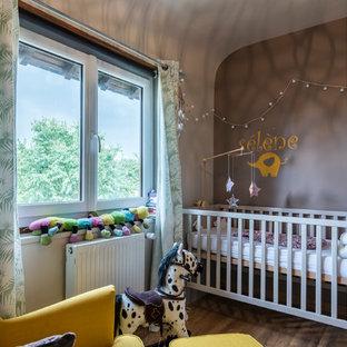 Cette image montre une chambre de bébé fille bohème avec un mur gris.