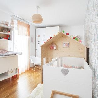 Exemple d'une chambre de bébé fille tendance avec un mur multicolore, un sol en bois brun et un sol marron.