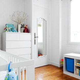 Aménagement d'une chambre de bébé garçon contemporaine de taille moyenne avec un mur blanc, un sol en bois brun et un sol orange.