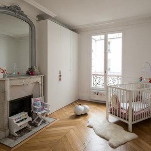 Réalisation d'une chambre de bébé neutre design de taille moyenne avec un mur blanc et un sol en bois clair.