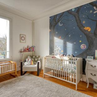 Inspiration pour une chambre de bébé design avec un mur blanc, un sol en bois brun et un sol marron.