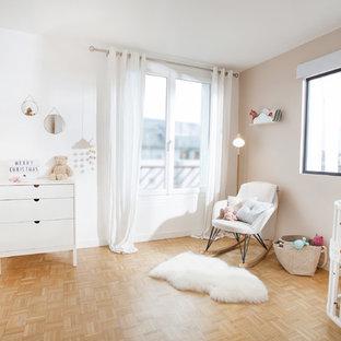 Idées déco pour une chambre de bébé neutre scandinave avec un mur blanc, un sol en bois clair et un sol beige.