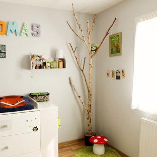 Aménagement d'une chambre de bébé garçon contemporaine de taille moyenne avec un mur blanc et un sol en bois brun.