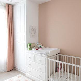 Diseño de habitación de bebé niña tradicional renovada, de tamaño medio, con paredes rosas y suelo de madera clara