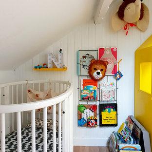 Idées déco pour une chambre de bébé garçon éclectique avec un mur blanc, un sol en bois brun et un sol marron.