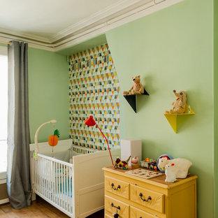Imagen de habitación de bebé neutra contemporánea, grande, con paredes verdes y suelo de madera clara