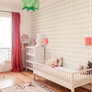 Idée de décoration pour une chambre de bébé fille tradition avec un mur vert et un sol en bois brun.
