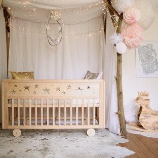 Aménagement d'une chambre de bébé fille romantique avec un mur blanc et un sol en bois brun.