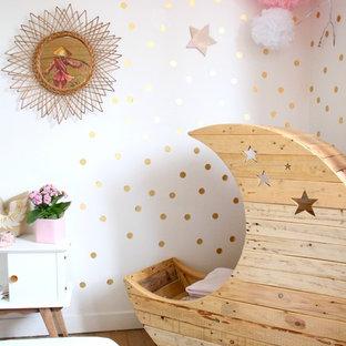 Inspiration pour une chambre de bébé fille traditionnelle avec un mur blanc et un sol en bois brun.