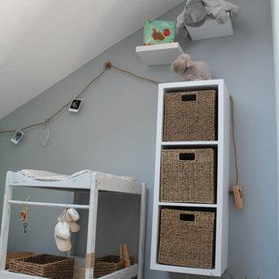 Imagen de habitación de bebé neutra de estilo de casa de campo, pequeña, con paredes multicolor y suelo de madera clara