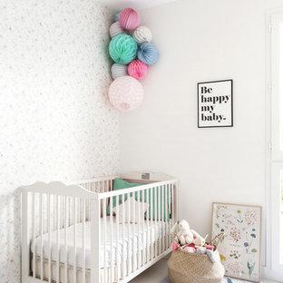 Imagen de habitación de bebé niña moderna, de tamaño medio, con paredes blancas y suelo de madera pintada