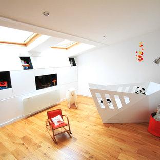 Idées déco pour une chambre de bébé neutre contemporaine de taille moyenne avec un mur blanc et un sol en bois brun.