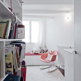 Idée de décoration pour une chambre de bébé neutre design de taille moyenne avec un mur blanc et un sol en bois foncé.