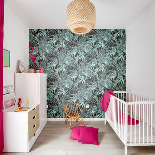 This is an example of a world-inspired nursery for girls in Paris with multi-coloured walls, light hardwood flooring and beige floors.