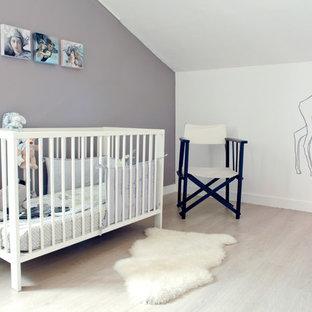 Exemple d'une grand chambre de bébé neutre tendance avec un mur gris, un sol en bois clair et un sol beige.