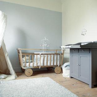 Exemple d'une chambre de bébé neutre tendance de taille moyenne avec un mur gris et un sol en bois clair.