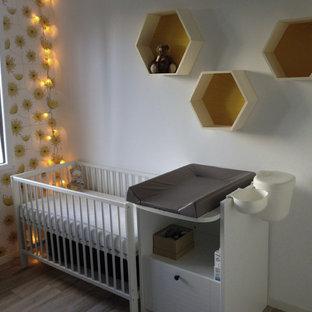 Cette image montre une petit chambre de bébé neutre minimaliste avec un sol en linoléum, un sol beige et un mur bleu.