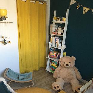 Imagen de habitación de bebé neutra minimalista, pequeña, con paredes azules, suelo de linóleo y suelo beige