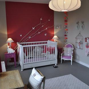 Diseño de habitación de bebé niña ecléctica, de tamaño medio, con paredes rojas y suelo gris