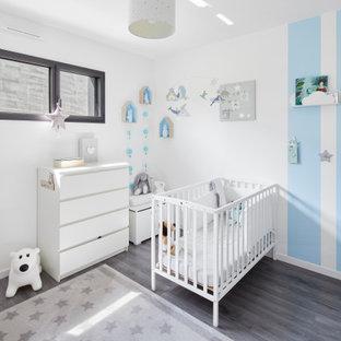 Idée de décoration pour une chambre de bébé garçon design de taille moyenne avec un mur bleu, sol en stratifié et un sol gris.