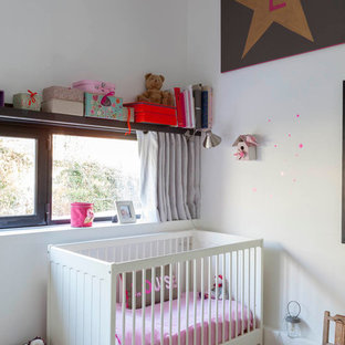 Mid-sized urban girl plywood floor and beige floor nursery photo in Paris with white walls
