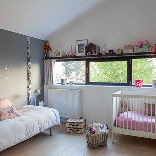 Imagen de habitación de bebé niña urbana, de tamaño medio, con paredes blancas, suelo de contrachapado y suelo beige