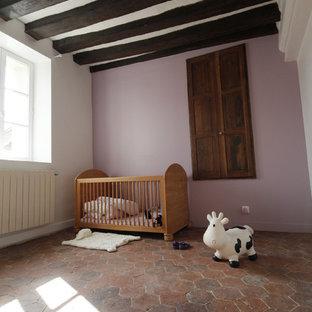 Exemple d'une grande chambre de bébé fille nature avec un mur rose et un sol en carreau de terre cuite.