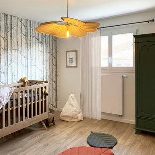 Réalisation d'une grand chambre de bébé garçon nordique avec un mur blanc, un sol en bois clair et un sol marron.