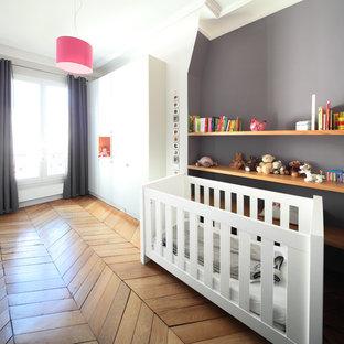 Cette image montre une grand chambre de bébé neutre design avec un mur gris et un sol en bois clair.