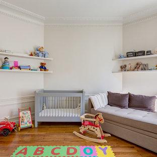 Inspiration pour une grande chambre de bébé neutre traditionnelle avec un mur blanc et un sol en bois brun.