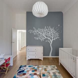 Cette image montre une chambre de bébé neutre nordique de taille moyenne avec un mur gris, un sol en bois brun et un sol marron.