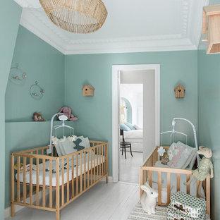 Foto di una cameretta per neonati neutra chic di medie dimensioni con pareti blu e pavimento in legno verniciato
