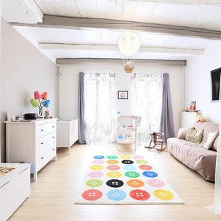 Exemple d'une grand chambre de bébé neutre scandinave avec un mur beige, un sol en bois clair et un sol beige.