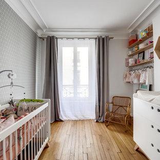 Cette image montre une chambre de bébé fille nordique de taille moyenne avec un mur gris et un sol en bois clair.