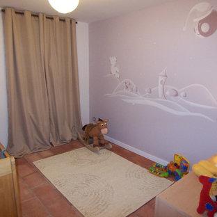 Cette photo montre une chambre de bébé neutre avec un mur beige, un sol en carreau de terre cuite et un sol rouge.