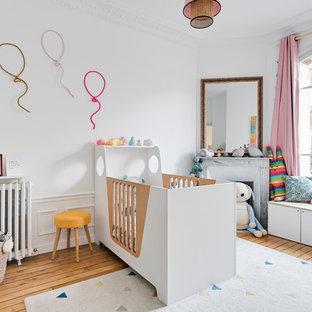 Exemple d'une chambre de bébé fille scandinave avec un mur blanc et un sol en bois clair.