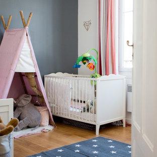 Réalisation d'une chambre de bébé fille tradition de taille moyenne avec un mur gris, un sol en bois brun et un sol marron.