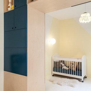 Ejemplo de habitación de bebé neutra actual con paredes amarillas y suelo blanco