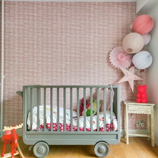 This is an example of a medium sized bohemian nursery for girls in Paris with pink walls, light hardwood flooring and beige floors.