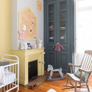 Exemple d'une chambre de bébé fille scandinave avec un mur jaune et un sol orange.