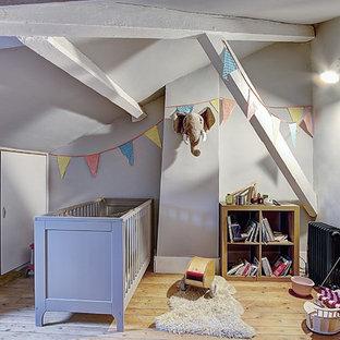 Aménagement d'une chambre de bébé neutre classique de taille moyenne avec un mur gris, un sol en bois clair et un sol beige.